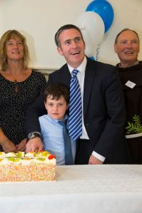 """22/07/2016. FREE TO USE IMAGE. Pictured on Friday 22nd July, at the official opening of  John's College Redevelopment. Pictured cutting the cake Sen. Grace O'Sullivan, Damien English T.D. Minister of State for Housing and Urban Renewel and his son Harvey and Fr. Pat Cogan ofm, Founding Director of Respond!. Picture: Patrick Browne Formal Opening of John's College Redevelopment  Stage One Completed: Ten Years of Redevelopment Planning/Construction is now completed.  On conclusion of the acquisition and planning, the actual re-construction of John's College began in March 2014 by Respond! Ltd and was completed in November 2016 by Mythen Construction, ahead of schedule. The impressive development includes 21 new apartments in the College, with a 10-bed group home and 36 new-build one-bed apartments overlooking the Folly. The total redevelopment costs came to €12 million. All of the residents in John's College came from the Waterford City and County Local Authority waiting list. The apartments cater mainly for Older People and people with specific needs and requirements who are capable of independent living.  On Friday 22nd July, the Minister of State for Housing and Urban Renewal, Damien English, T.D. performed the official opening of the John's College campus in Waterford with a large crowd of distinguished guests in attendance. The Bishop of Waterford and Lismore, Very Reverent Alphonsus Cullinan and Dean Maria Jansson carried out a blessing of the campus. The recently elected Mayor of Waterford City and County, Cllr. Adam Wyse was in attendance and was highly impressed with the redevelopment.  According to the John's College Facilities Co-ordinator, David Phelan: """"All of the residents have now moved in and are very happy with their accommodation and the support services offered in John's College. We are currently running a number of activation and recreational programmes for our tenants and the wider Waterford community to counteract"""
